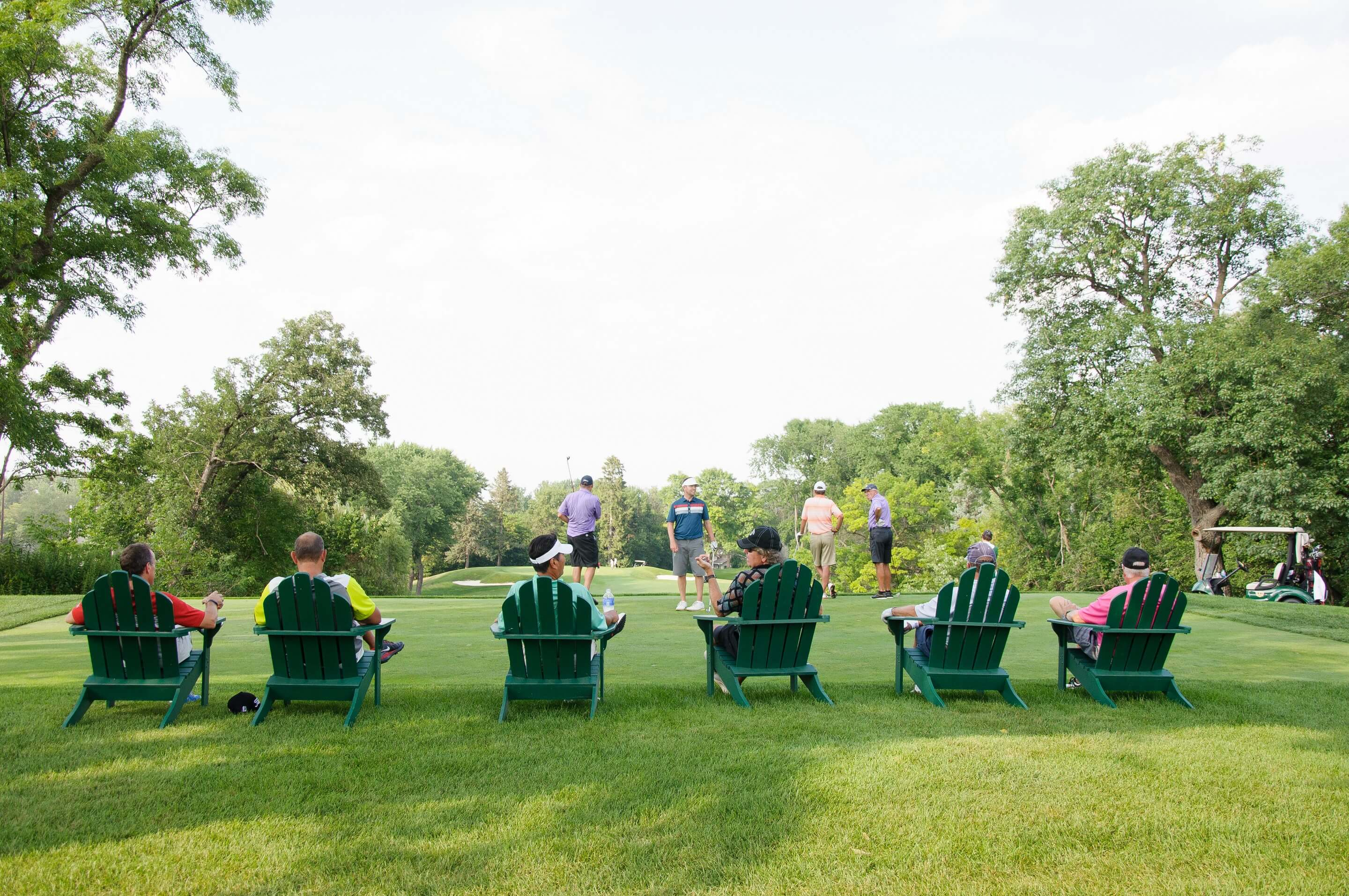 Golfers in chairs watching golf event